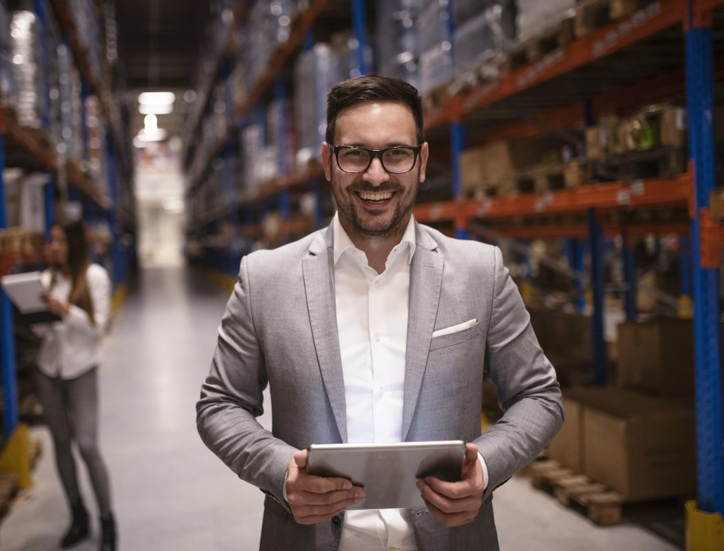 Cheerful and successful middle aged caucasian manager businessman holding tablet computer in large warehouse organizing distribution.